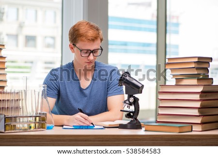 Young student tired and exhausted preparing for chemistry exam