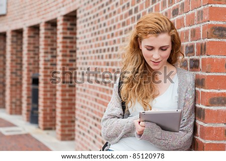 Young student using a tablet computer outside a building