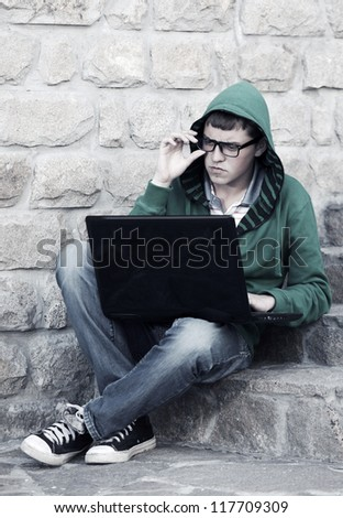 Young student using laptop on the steps