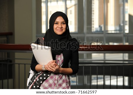 Young Student wearing a veil and holding a copybook with college building on background