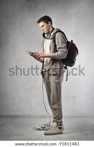 Young student wearing headphones and holding a book