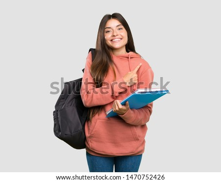 Young student woman holding notebooks pointing to the side to present a product over isolated grey background #1470752426