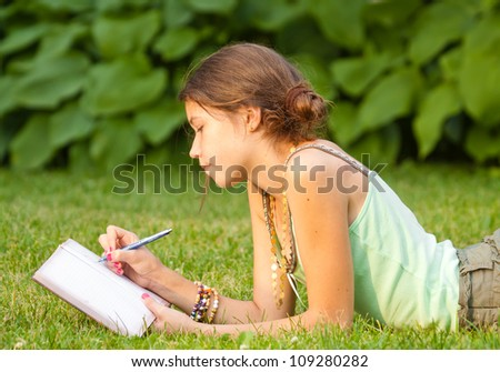 Young student writing into her notebook