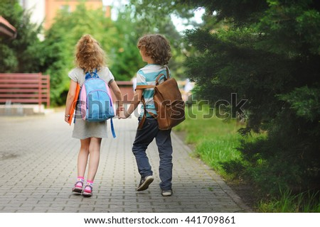 Young students, boy and girl, going to school. They hold hands. They hold hands. Children behind shoulders have satchels. Warm day in an early autumn.