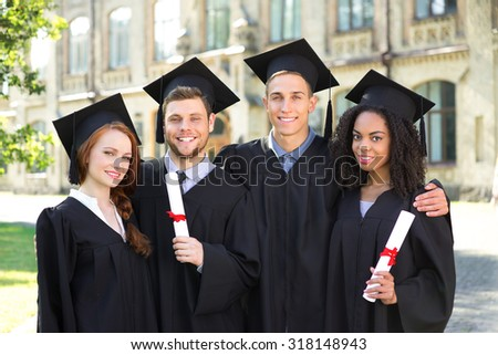 Young students dressed in black graduation gown. Campus as a background. Boys and girls smiling, hugging, holding diplomas and looking at camera