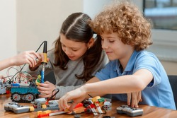 Young students, girl and boy, working in pair, putting a robotics kit together. Simple project for engineering class.