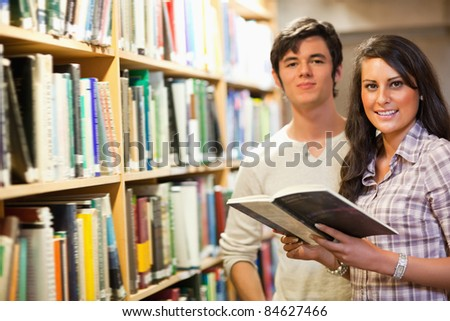 Young students holding a book in a library