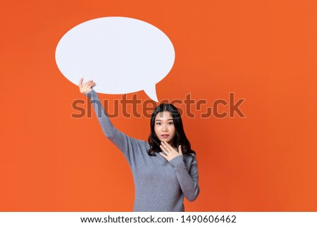 Young stunned Asian girl in gray t-shirt holding empty speech bubble isolated on orange background