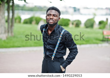 Young stylish african american man wear on all black with suspenders posed outdoor.