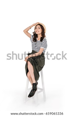 young stylish asian woman posing while sitting on chair isolated on white