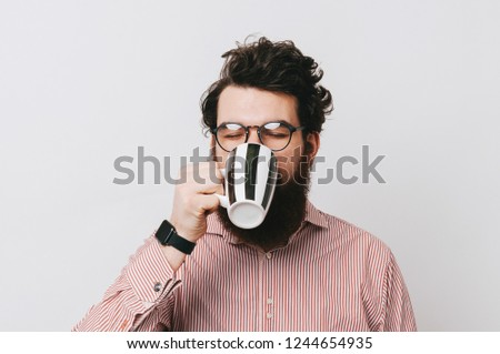 Young stylish bearded man drinking and enjoying his mug of coffee, or tea, or hot chocolate. Hipster wearing shirt, glasses and smart watch.