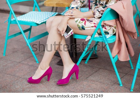 Stock Photo young stylish beautiful woman sitting in city cafe in street, spring fashion trend style,  long legs, pink heeled shoes, holding mobile phone in hands, close-up details, accessories