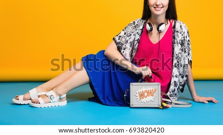 young stylish beautiful woman, summer fashion trend, yellow studio background, blue skirt, pink top, apparel, white sandals, handbag, cool, modern, colorful, accessories, footwear, legs close up
