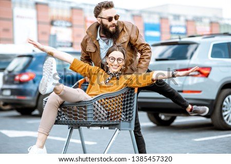 Young stylish coupe having fun riding with shopping cart on the outdoor parking near the supermarket #1385457320
