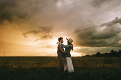 young stylish couple hugging on meadow at beautiful sunset