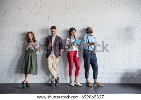 young stylish friends using digital devices while standing near brick wall #659065327