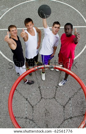Young stylish group of teenage boys standing under a basketball hoop giving thumbs up sign.