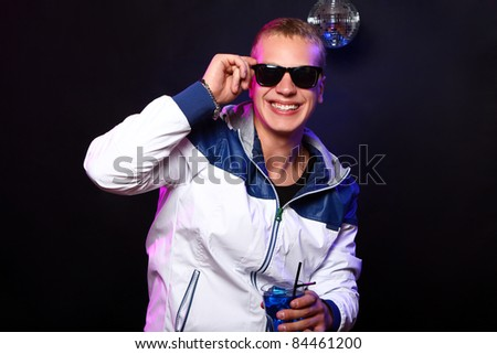 Young stylish guy with a blue cocktail in the nightclub