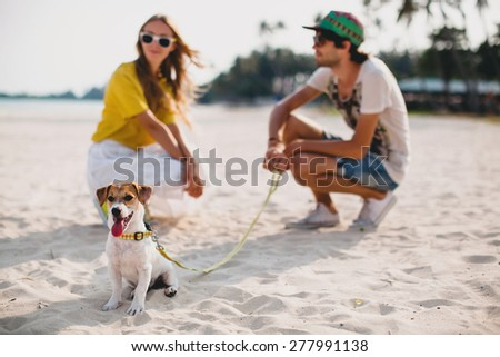 young stylish hipster couple in love walking playing dog puppy jack russell in tropical beach, white sand, cool outfit, romantic mood, having fun, sunny, man woman together, horizontal, vacation