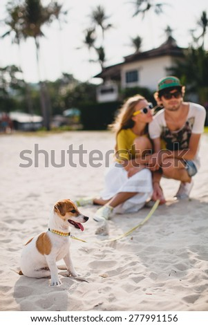 young stylish hipster couple in love walking playing dog puppy jack russell in tropical beach, white sand, cool outfit, romantic mood, having fun, sunny, man woman together, vacation