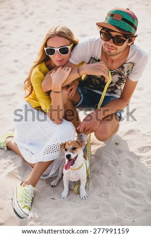 young stylish hipster couple in love walking playing dog puppy jack russell in tropical beach, sitting on white sand, cool outfit, romantic mood, having fun, sunny, man woman together, vacation