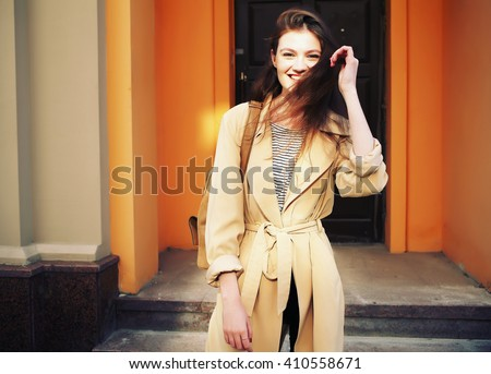 Young stylish hipster girl wearing modern trench coat walking in urban city smiling happy. Caucasian female model in her 20s. Stock photo ©