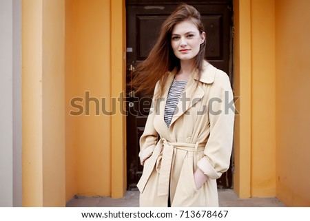 Young stylish hipster girl wearing modern trench coat walking in urban city smiling happy. Caucasian female model in her 20s. Fall fashion Stock photo ©
