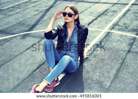 young stylish hipster woman outdoor, wearing sunglasses, black leather jacket, jeans overall, suede sneakers, urban fashion