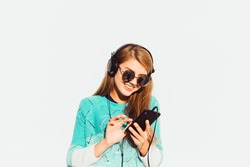 Young stylish hipster woman wearing autumn clothes on white, vintage midi skirt,big earphones, walking on the street at nice sunny summer day, bright fresh colors.