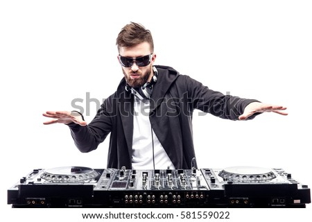 Young stylish man in black sunglasses posing behind mixing console on white studio background.