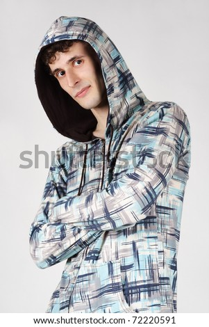 young stylish man in hood standing with crossed hands, looking at camera