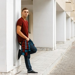 Young stylish man in stylish red t-shirt in a plaid trendy shirt in fashionable blue jeans in sneakers posing outdoors near a white vintage building on a summer day. Handsome guy enjoys a walk.