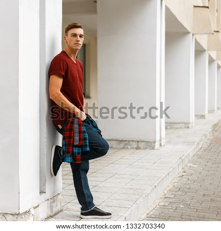 Young stylish man in stylish red t-shirt in a plaid trendy shirt in fashionable blue jeans in sneakers posing outdoors near a white vintage building on a summer day. Handsome guy enjoys a walk. #1332703340