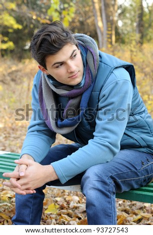 Young stylish man portrait sitting in autumn park. Outdoor.