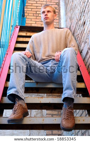 Young stylish man with blonde hair sit on stairs near brick wall.