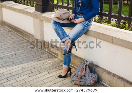 young stylish pretty woman, hands holding a phone, denim shirt and jeans, high heel shoes, hat, backpack, sunny day, good weather, city street, vacation europe, travel, detail, cool accessories