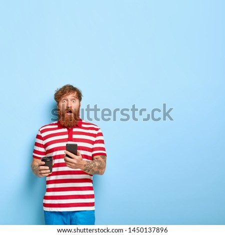 Young stylish redhead man feels amazed, reads media news message online on cellular, shocked to have problems with new gadget, enjoys drinking coffee from disposable cup, wears striped t shirt