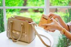 Young stylish woman hand holding brown wallet with credit card take out money for pay in restaurant. Beige color leather handbag put on white table background.