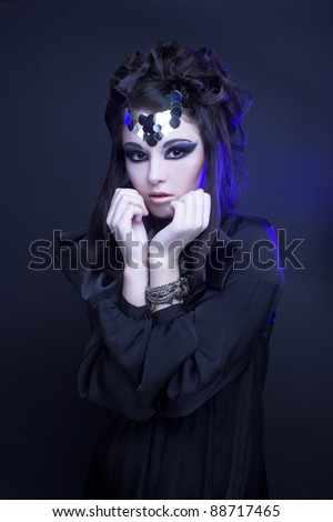 Young stylish woman in black dress with artistic visage with smokey-eyes