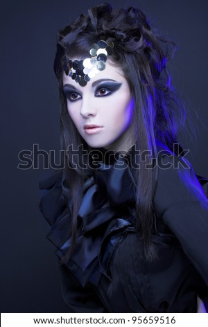 Young stylish woman in black dress with artistic visage with smokey-eyes standing  in blue light