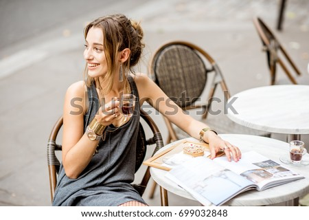 Young stylish woman in gray dress drinking coffee outdoors at the cafe in Paris