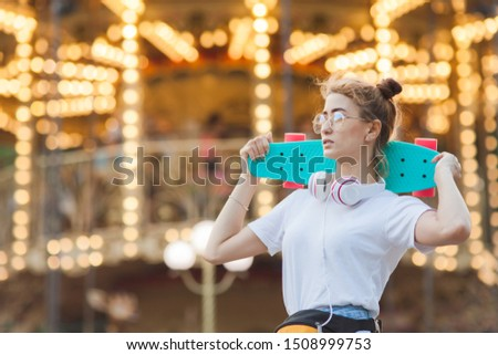 Young stylish woman in stylish youth clothes with a skateboard on her shoulders having fun in amusement park against background of illumination.