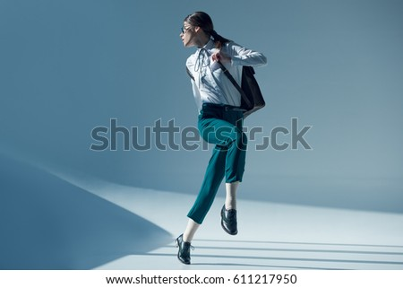 young stylish woman in white shirt, green trousers and glasses looking away while jumping