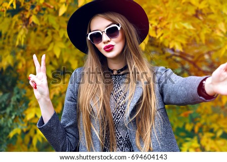 Young stylish woman making selfie in autumn golden leaves park, stylish grunge elegant trendy outfit, dress, gray coat , sunglasses ant vintage hat, making selfie and having fun. Kiss on camera,