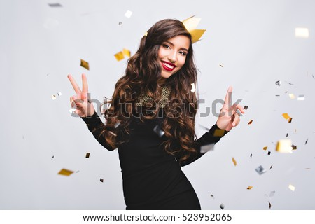 Shutterstock Young stylish woman on white background drinking champagne, celebrating new year, wearing black dress and yellow crown, happy carnival disco party, sparkling confetti, holding glass, having fun