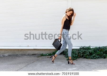 Young stylish woman wearing black cami top, blue cropped denim jeans, black high heel sandals and holding bag walking in the city street. Trendy casual outfit for summer or spring. Street fashion.