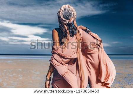 young stylish woman with fashionable boho accessories on the beach windy time