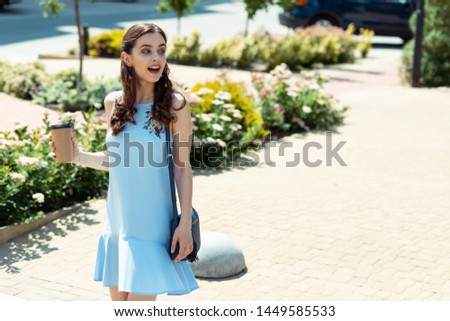 Young stylish woman. Young stylish woman wearing blue summer dress drinking coffee and walking