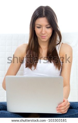 Young successful attractive female sitting on a sofa with modern laptop typing on keyboard