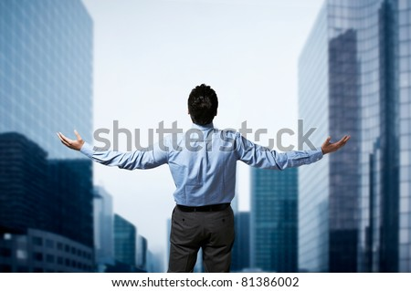 Young successful business man standing with arms wide open in front of buildings business center